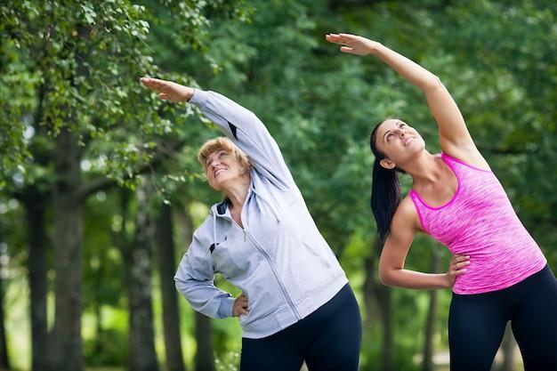 Jovem e mulher sênior fazendo esportes no parque
