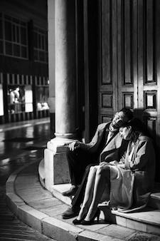 Jovem e mulher sentada perto da porta na rua