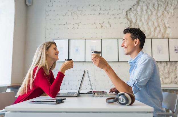 Jovem e mulher sentados à mesa, cara a cara, trabalhando no laptop em um escritório colaborativo