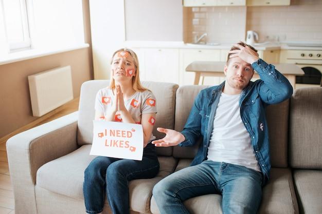 Jovem e mulher têm dependência de mídia social. dependência de smartphones. implorando por gostos. homem desapontado.