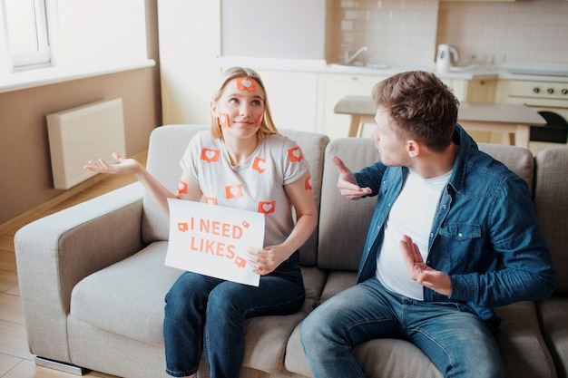 Jovem e mulher têm dependência de mídia social. dependência de smartphones. mulher feliz no sofá. cara preocupado.