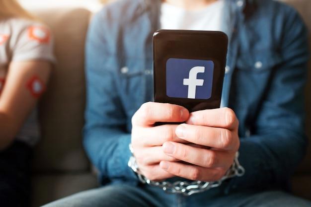 . jovem e mulher têm dependência de mídia social. segurando o telefone nas mãos. correntes ao redor do pulso.