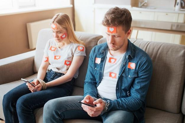 . jovem e mulher têm dependência de mídia social. sentado no sofá. segurando os telefones nas mãos. reféns.