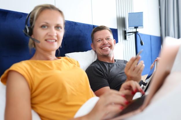 Jovem e mulher trabalham remotamente enquanto estão deitados na cama, introdução e desenvolvimento de negócios