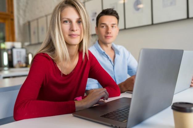 Jovem e mulher trabalhando em um laptop em uma sala de escritório em parceria com espaço aberto,