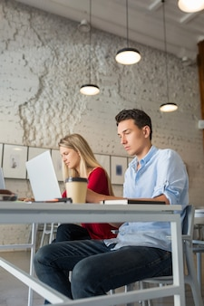 Jovem e mulher trabalhando em um laptop em uma sala de escritório em parceria com espaço aberto