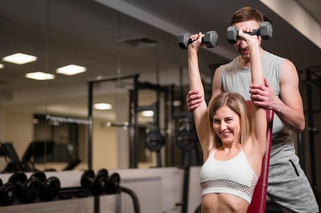 Jovem e mulher treinando na academia