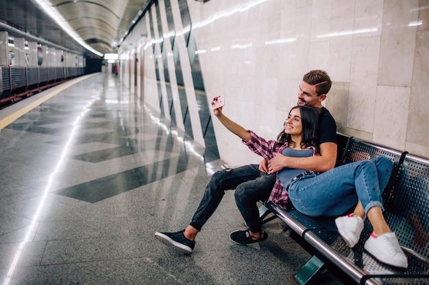 Jovem e mulher usam no subsolo. casal no metrô. jovem mulher tomando selfie de si mesma e namorado na estação de metro vazia. sorria e posar. história de amor.