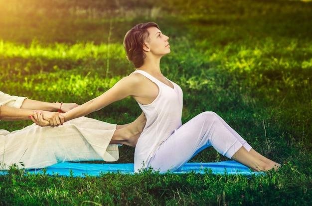 Jovem e mulher vestida com uma túnica branca, fazendo massagem tailandesa com exercícios de ioga, sentado no tapete. parque de verão ensolarado com gramado verde ao fundo