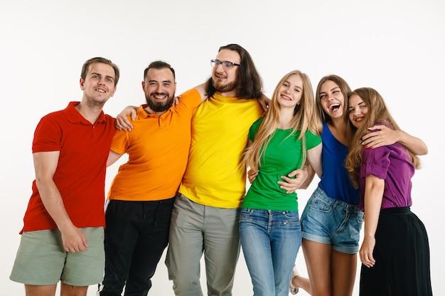 Jovem e mulher vestidos com as cores da bandeira lgbt na parede branca. modelos caucasianos com camisas brilhantes.