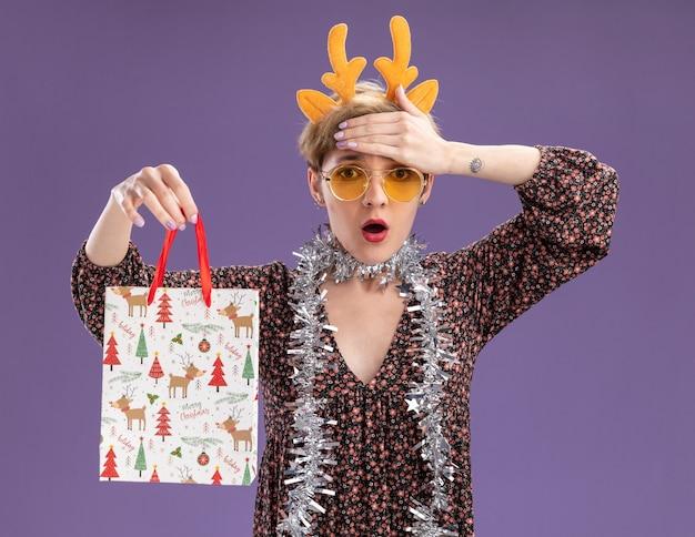Jovem e preocupada com uma faixa na cabeça com chifres de rena e uma guirlanda de ouropel em volta do pescoço com óculos segurando uma sacola de presente de natal, mantendo a mão na testa isolada na parede roxa