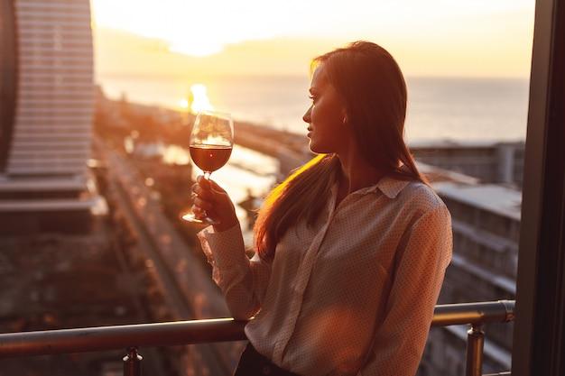 Jovem é relaxar e beber um copo de vinho tinto na varanda ao pôr do sol à noite
