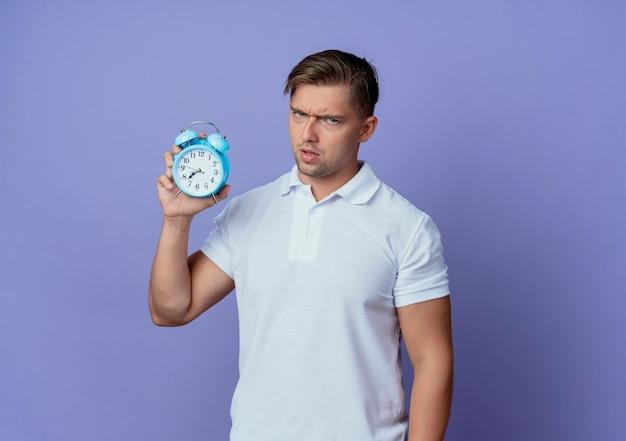 Jovem e rigoroso estudante bonito segurando um despertador isolado no azul