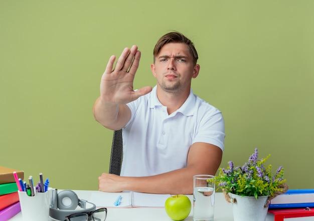 Jovem e rigoroso estudante bonito sentado à mesa com as ferramentas da escola, mostrando um gesto de parada em verde oliva