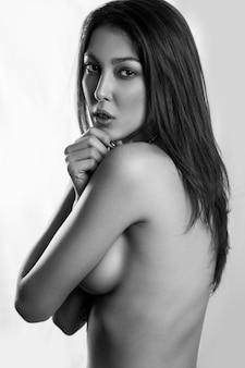 Jovem e sensual modelo nu olhando sedutoramente para a câmera isolada no fundo branco