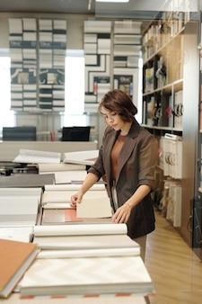 Jovem e séria assistente de loja ou gerente de estúdio de design de interiores olhando amostras de novos papéis de parede perto de uma mesa grande