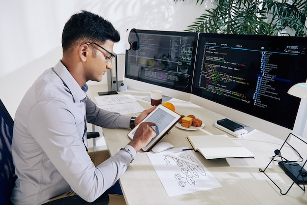 Jovem e sério desenvolvedor indiano de software verificando o mapa mental no tablet ao planejar o trabalho no projeto