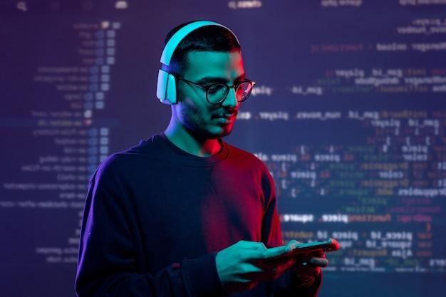 Jovem e sério testador árabe em fones de ouvido sem fio examinando o novo aplicativo no gadget, fundo de codificação