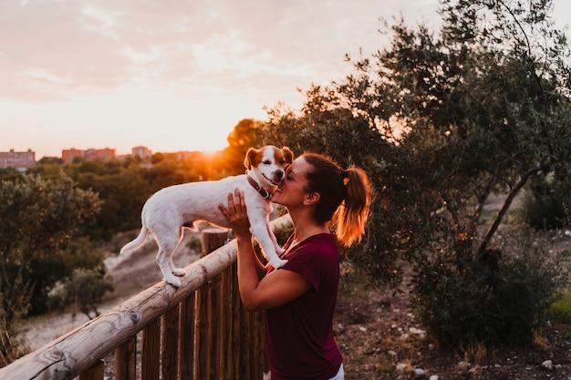 Jovem e seu cão pequeno bonito jack russell terrier assistindo o pôr do sol ao ar livre em um parque