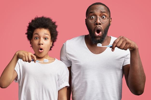 Jovem e seu filho com cabelo encaracolado segurando escovas de dente