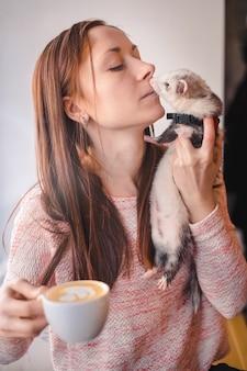 Jovem e seu furão de estimação no café
