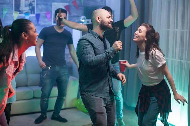 Jovem e seu melhor amigo cantando no microfone na festa.