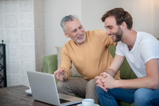 Jovem e seu pai assistindo algo online e parecendo envolvidos