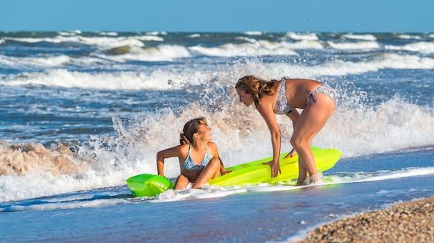 Jovem e sua filha com inflável na beira-mar