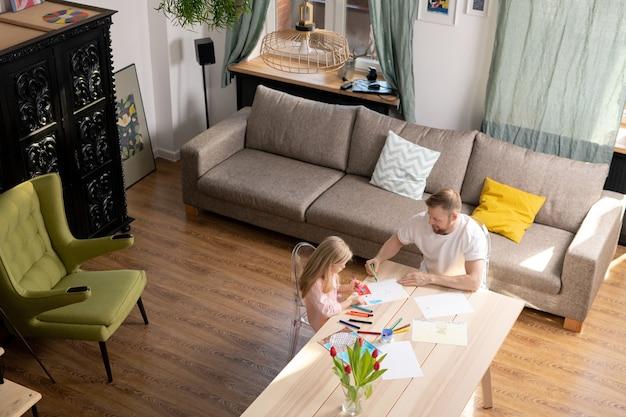Jovem e sua filhinha fofa em trajes casuais desenhando juntos enquanto o pai ensina uma menina com idade pré-elementar a fazer isso