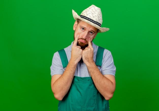 Jovem e triste jardineiro eslavo bonito de uniforme e chapéu olhando para baixo das pálpebras