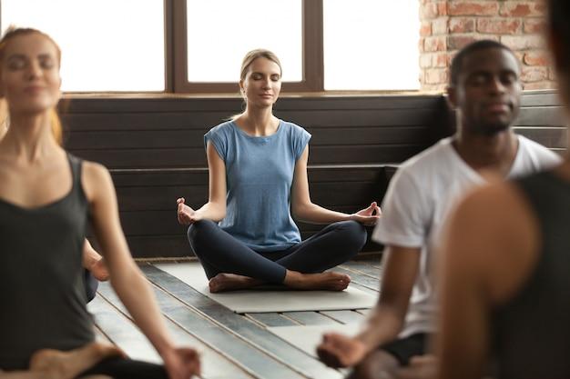 Jovem e um grupo de pessoas sentadas em sukhasana