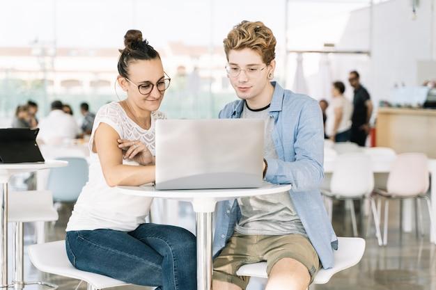 Jovem e uma garota trabalhando em conjunto com um laptop em um coworking
