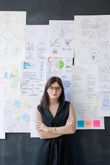 Jovem economista confiante com os braços cruzados ao lado do quadro-negro com fluxogramas e diagramas em papéis