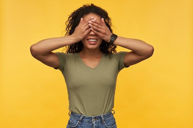 Jovem elegante afro-americana, usa camiseta verde com penteado afro, olhos fechados com os braços e sorri amplamente