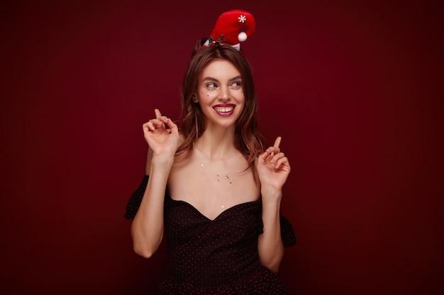 Jovem elegante alegre com maquiagem de noite levantando os dedos indicadores e sorrindo feliz, curtindo o baile de máscaras da festa de natal enquanto posa