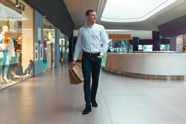 Jovem elegante andando em um shopping com sacolas ecológicas na mão com mercadorias e roupas. vendas, desconto esgotado conceito. esgotado sazonalmente.