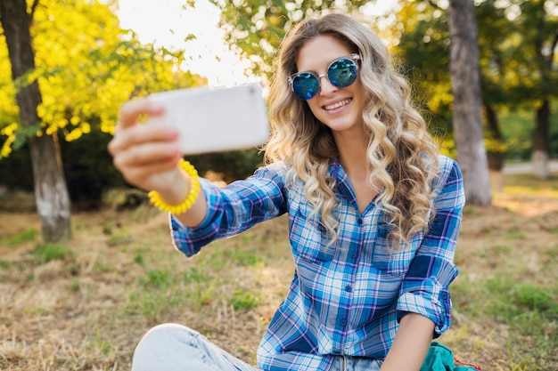 Jovem elegante atraente loira sorridente sentada no parque, estilo casual de verão