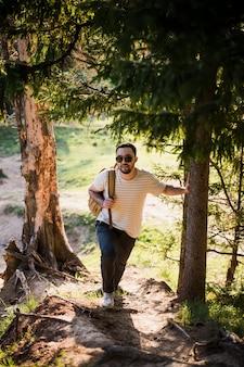 Jovem elegante bonito vestindo camiseta branca e óculos de sol com mochila na mão está viajando na floresta. posando na câmera perto de árvore