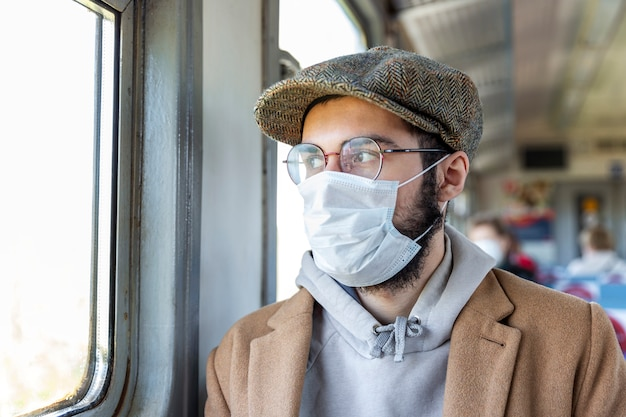Jovem elegante com barba, óculos e uma máscara médica em um trem olha pela janela. regime de auto-isolamento e distância social durante a pandemia de coronavírus. fechar-se. medidas de precaução.