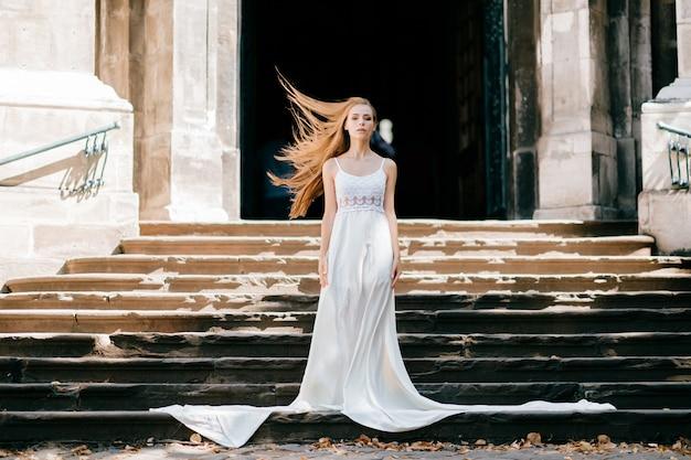 Jovem elegante com cabelo esvoaçante em um longo vestido branco, posando nas escadas do antigo palácio