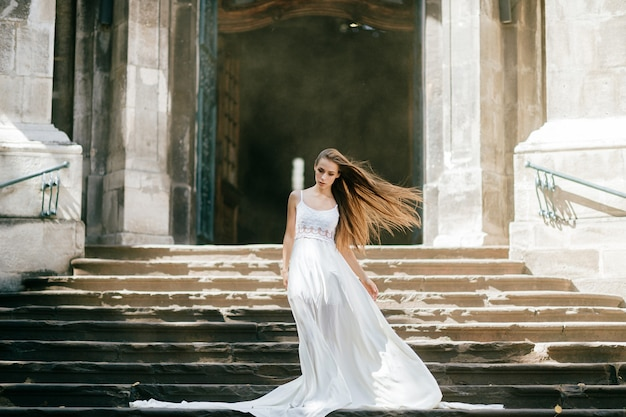 Jovem elegante com cabelo esvoaçante em um longo vestido branco, posando nas escadas do antigo palácio Foto Premium