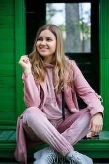 Jovem elegante com cabelo loiro de aparência europeia sentada na escada, vestida com um terno rosa, roupas casuais