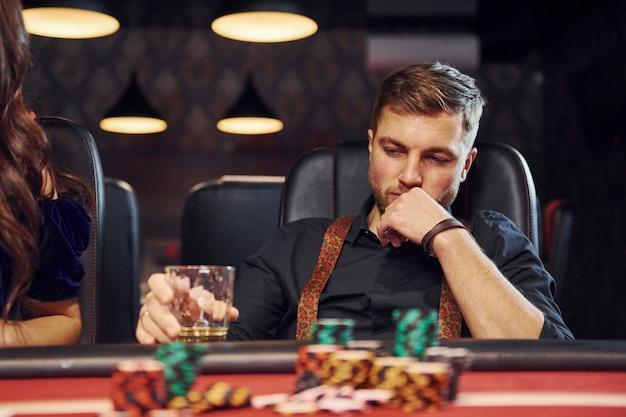 Jovem elegante com copo de álcool senta-se no cassino e joga jogo de pôquer