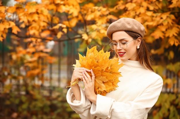 Jovem elegante com folhas no parque outono