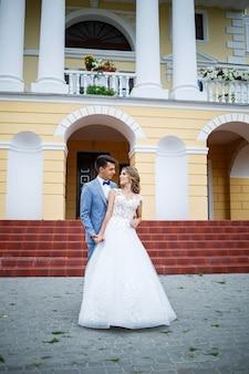 Jovem elegante com o traje do noivo e da noiva linda garota em um vestido branco com um trem andando no fundo de uma grande casa com colunas no dia do casamento
