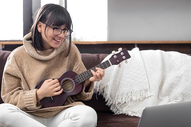 Jovem elegante com óculos aprende a tocar ukulele. conceito de educação online, educação em casa.