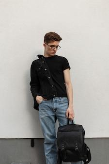 Jovem elegante com penteado em jaqueta jeans preta em jeans com óculos com mochila de couro fica e olha para baixo perto de um edifício vintage na cidade. cara urbano. moda casual americana.