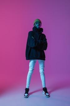 Jovem elegante com roupa de estilo moderno de rua isolada em uma parede gradiente em luz de néon.
