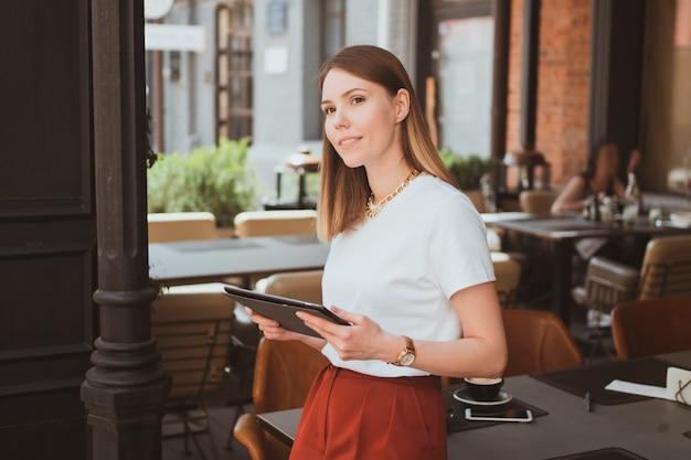 Jovem elegante com tablet digital trabalhando em um café de rua