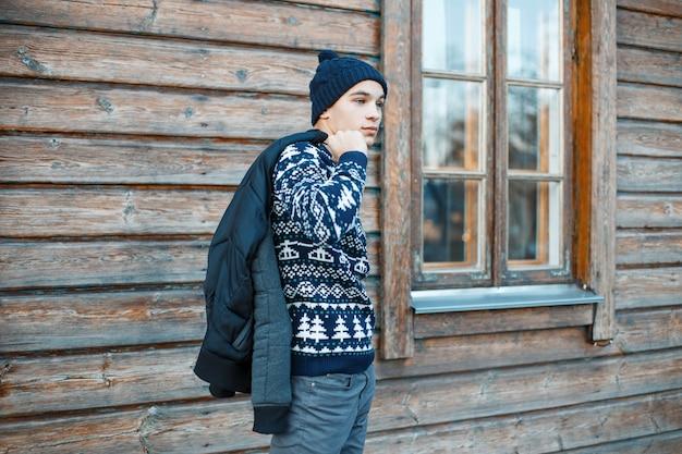 Jovem elegante com um chapéu de malha azul com uma camisola vintage com um padrão de natal branco em jeans da moda com uma jaqueta de inverno em pé perto de uma casa de campo de madeira marrom. cara bonito.